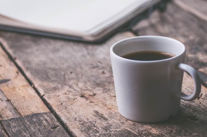 Anbaco - kopje koffie en notitieboek op oude houten tafel - Bloggen, online werken en online geld verdienen.